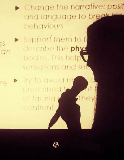 Silhouette image of Mine Conkbayir against the background of her presentation