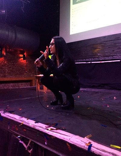 Image of Mine Conkbayir crouching during a presentation